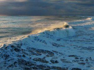 Big wave crashing wind blowing