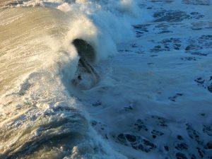 Surfer in wave at Oceanside Beach, CA