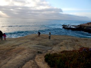 four people bluff overlooking Ocean Sunset Cliffs Natural Park