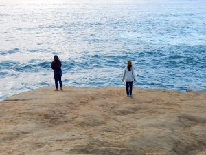 two girls on bluff overlooking Ocean