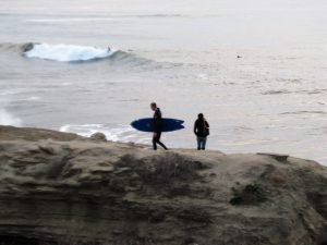 surfer and person walking bluff, ocean background