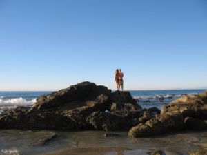 Dike Rock two people standing on wet sandy beach