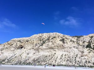 Paraglider Blacks Beach cliffs people sand