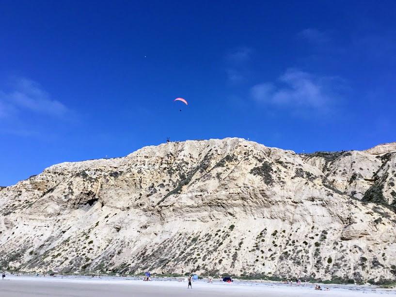Paraglider Blacks Beach cliffs people sand
